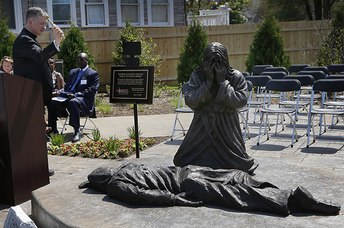 Cardinal Cupich blesses a statue of Jesus weeping over a gunshot victim at Catholic Charities' new Father Augustus Tolton Peace Center on May 24, 2018.